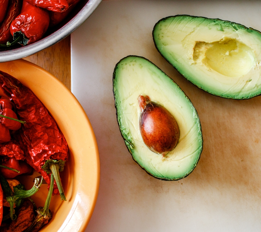 Peppers and an avocado sit on a table, ready for cooking