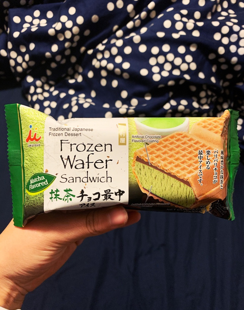 Ice cream sandwich held out by hand in front of black background