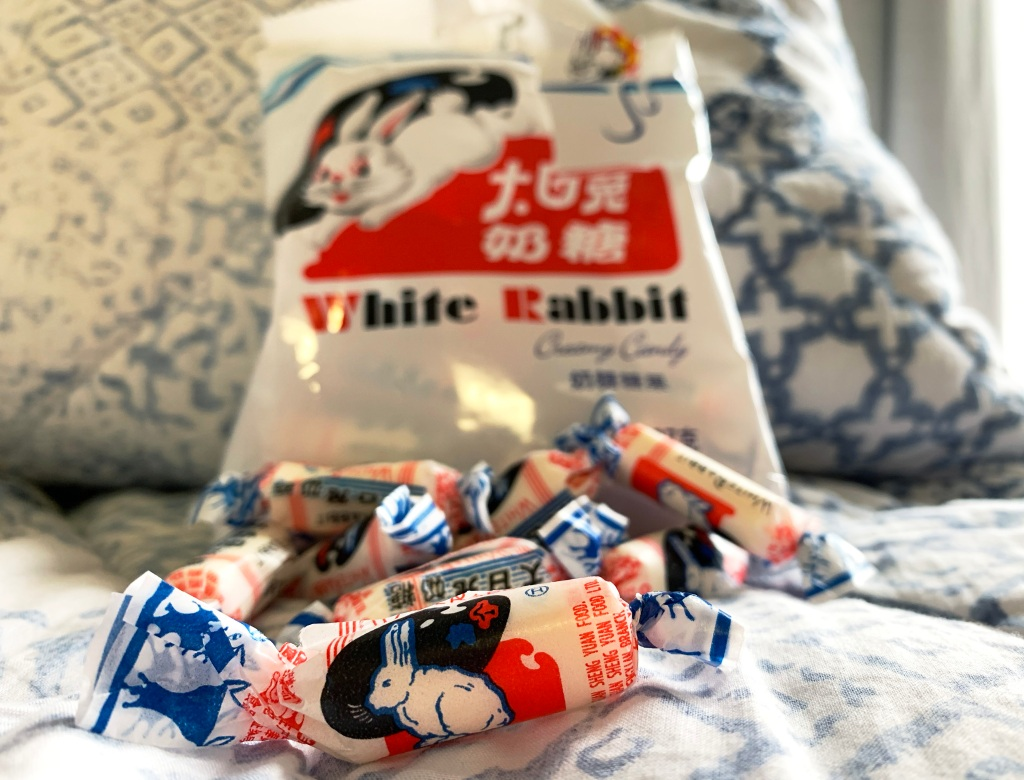 white rabbit candies opened on a bed with blue bedsheets
