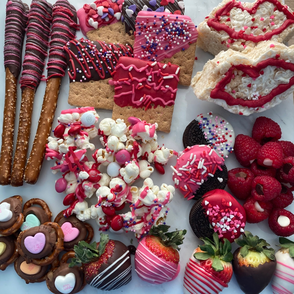 red and pink colored various valentines day treats including popcorn, pretzels, Oreos, strawberries, Rice Krispie treats, raspberries all dipped or decorated with chocolate