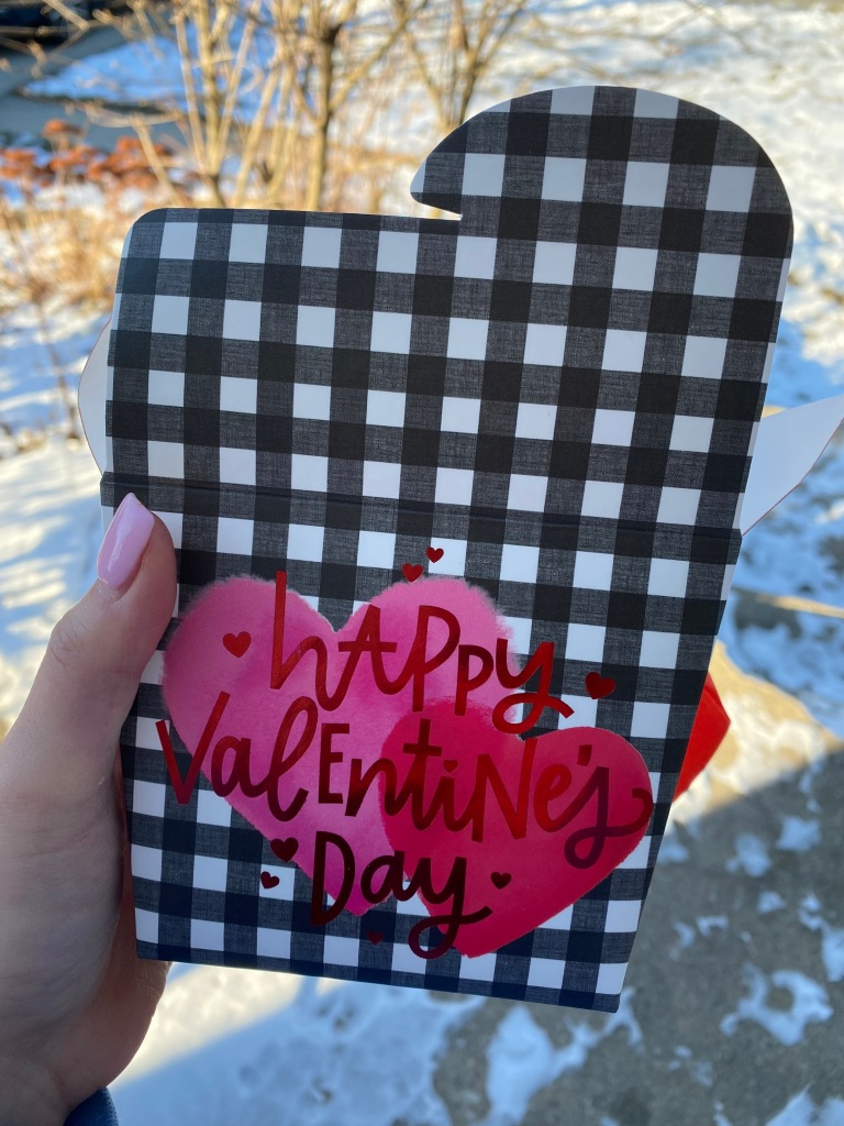 takeout container shaped box with the words happy Valentine's Day on the front. The box is held by a hand with pink nail polish in front of snow
