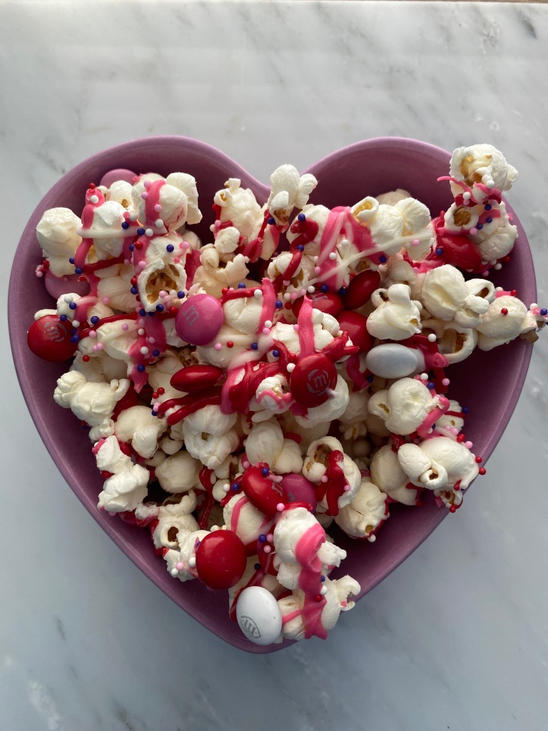 popcorn topped with colorful chocolate, red and pink M&Ms, and sprinkles
